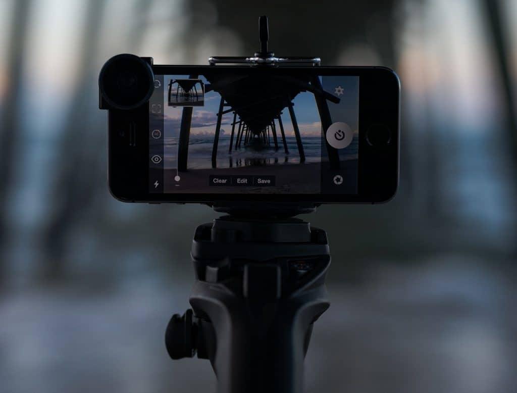 Na foto um celular conectado a um monopé com a tela mostrando uma praia.