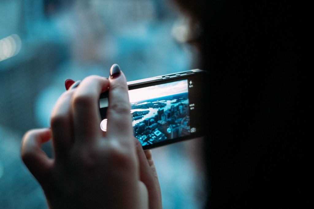 Mão feminina fotografando com um celular.
