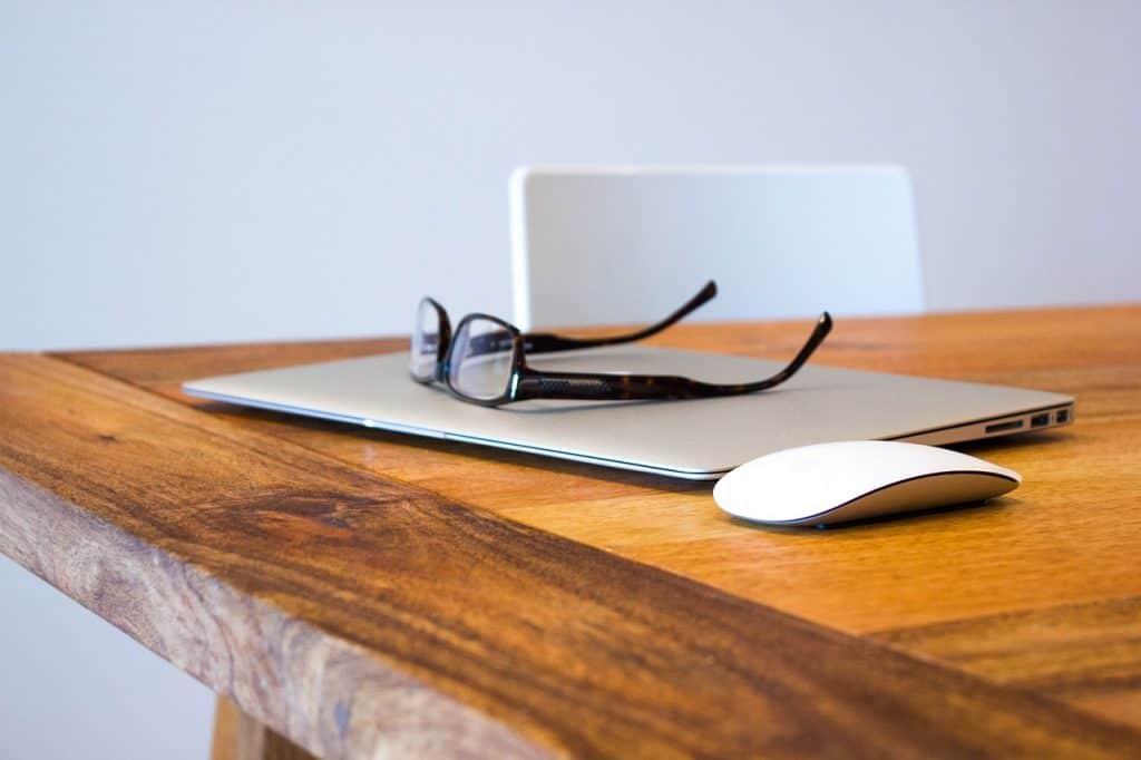Em cima de uma mesa há um Macbook embaixo de óculos de grau e ao lado de um mouse.