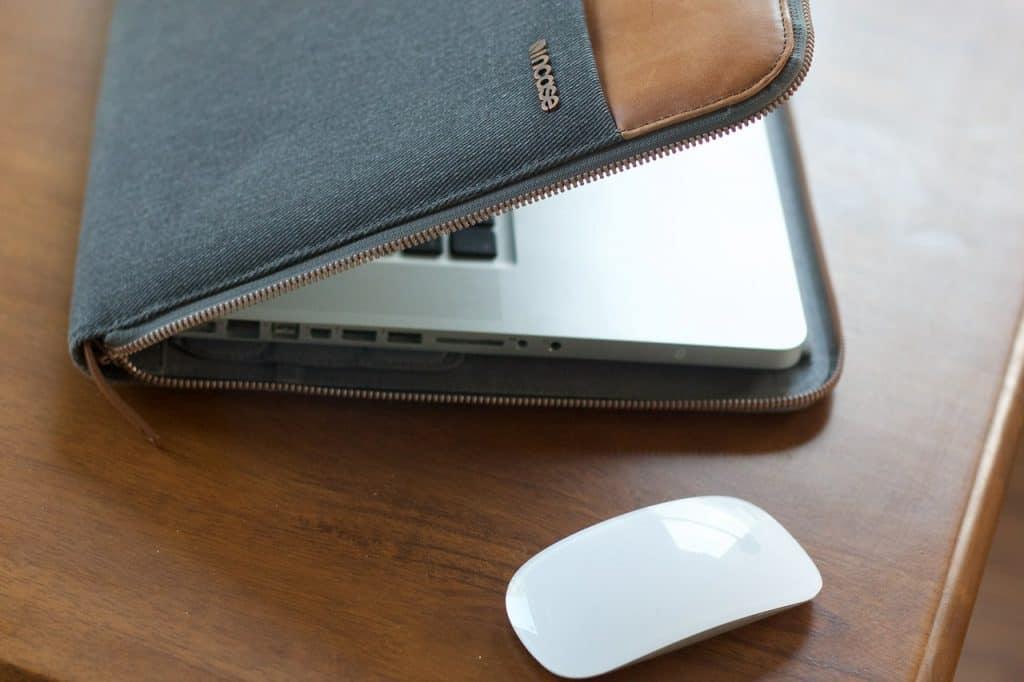 Um Macbook semiaberto e uma capa com zíper acima de uma mesa que também tem um mouse.