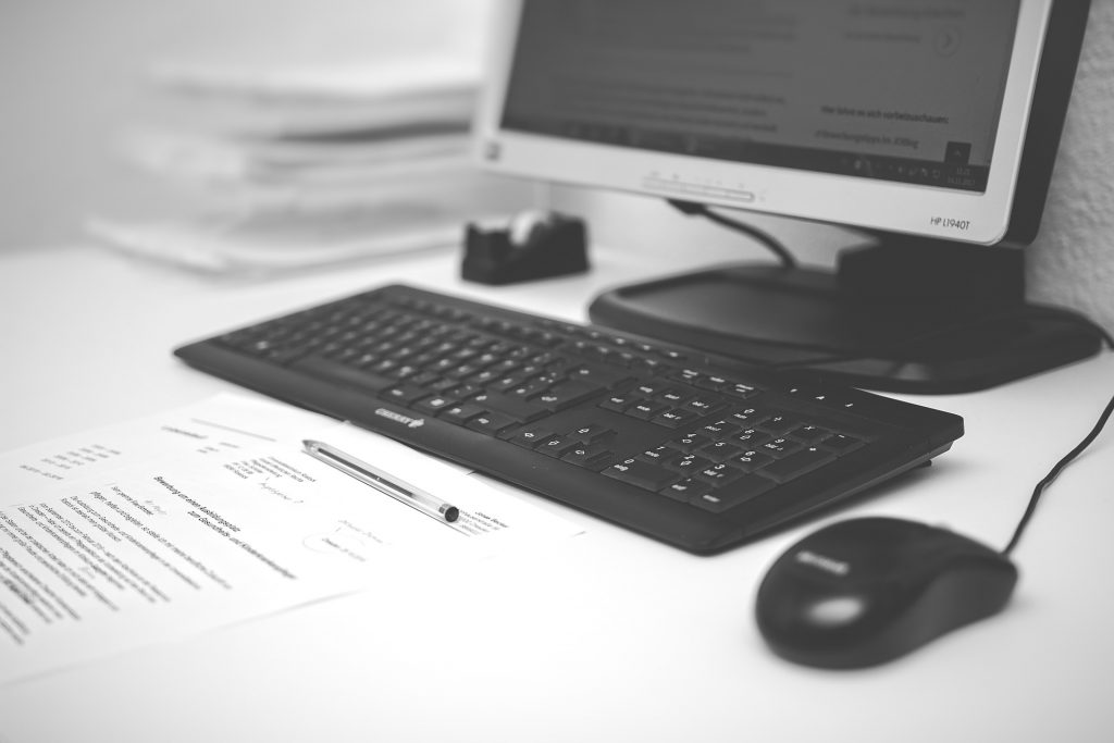 uma mesa de escritório com computador, mouse, teclado, papel e caneta