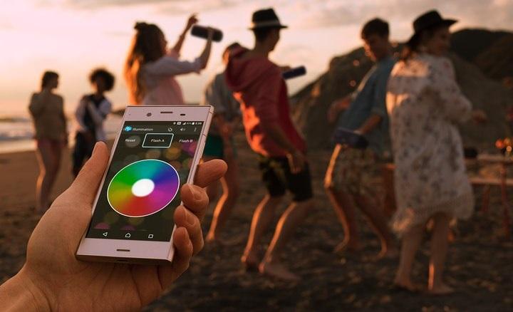 Na foto a mão de uma pessoa segurando um celular com pessoas ao fundo dançando.
