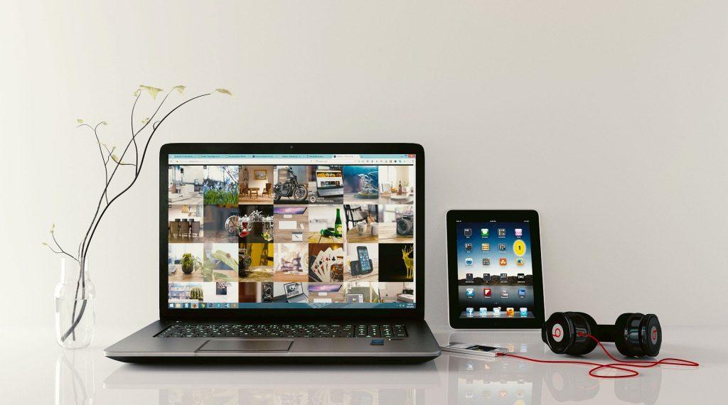 Notebook, tablet e fone de ouvido dispostos na mesa.