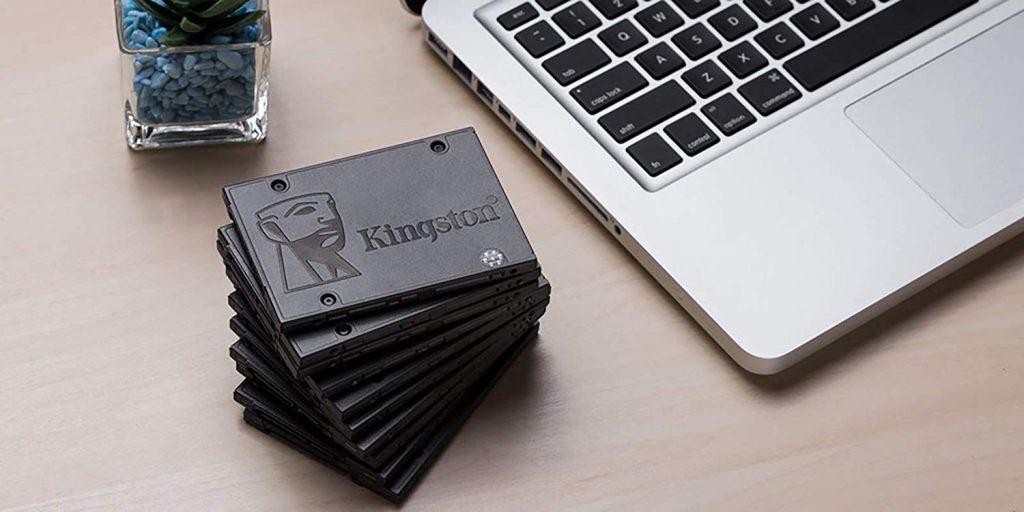 Vários SSDs Kingston empilhados com notebook ao lado.