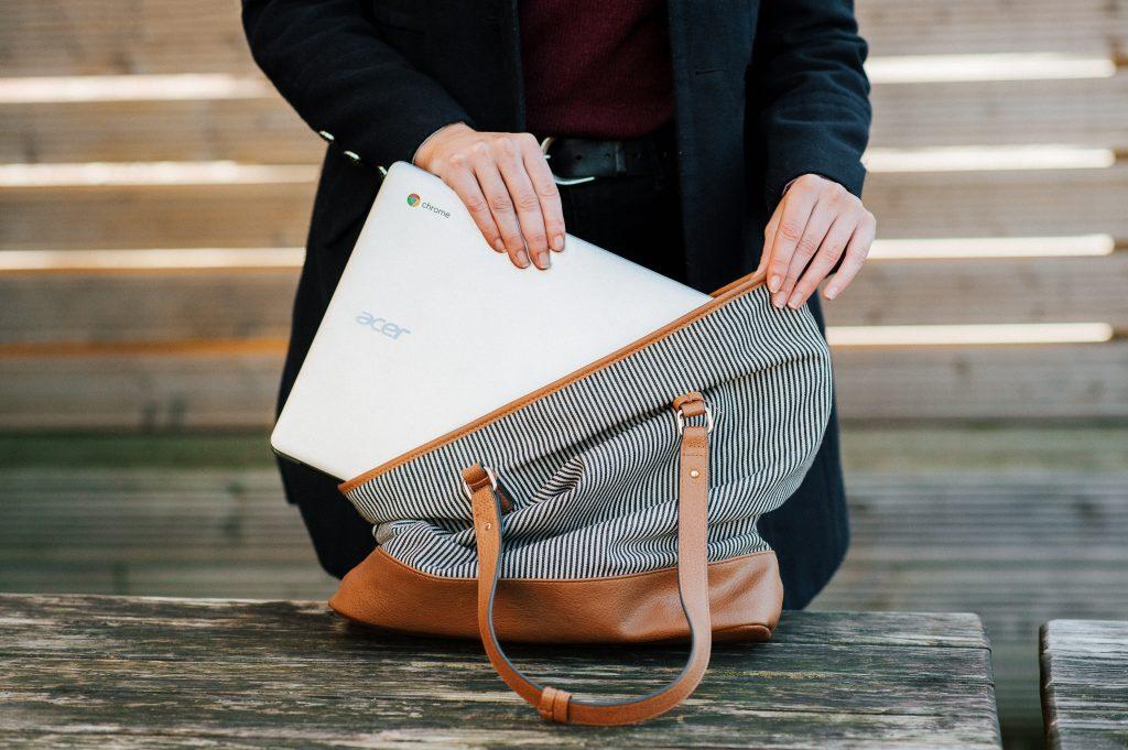 Imagem de uma mulher guardando um Chromebook na bolsa.