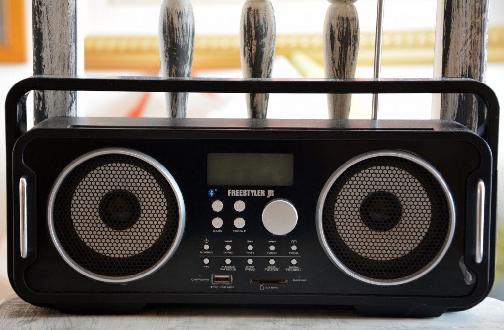 Imagem mostra um rádio portátil sobre uma cadeira. Entre botões de seu painel frontal, há o símbolo de conexão bluetooth.