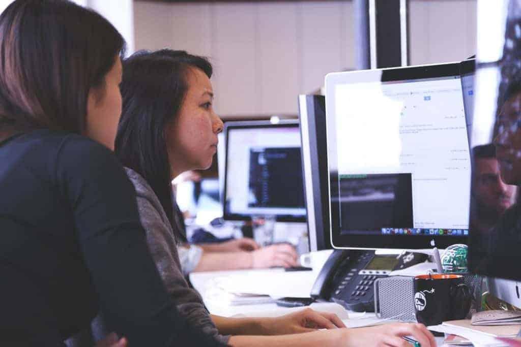 Na foto duas mulheres olhando para uma computador em um escritório.