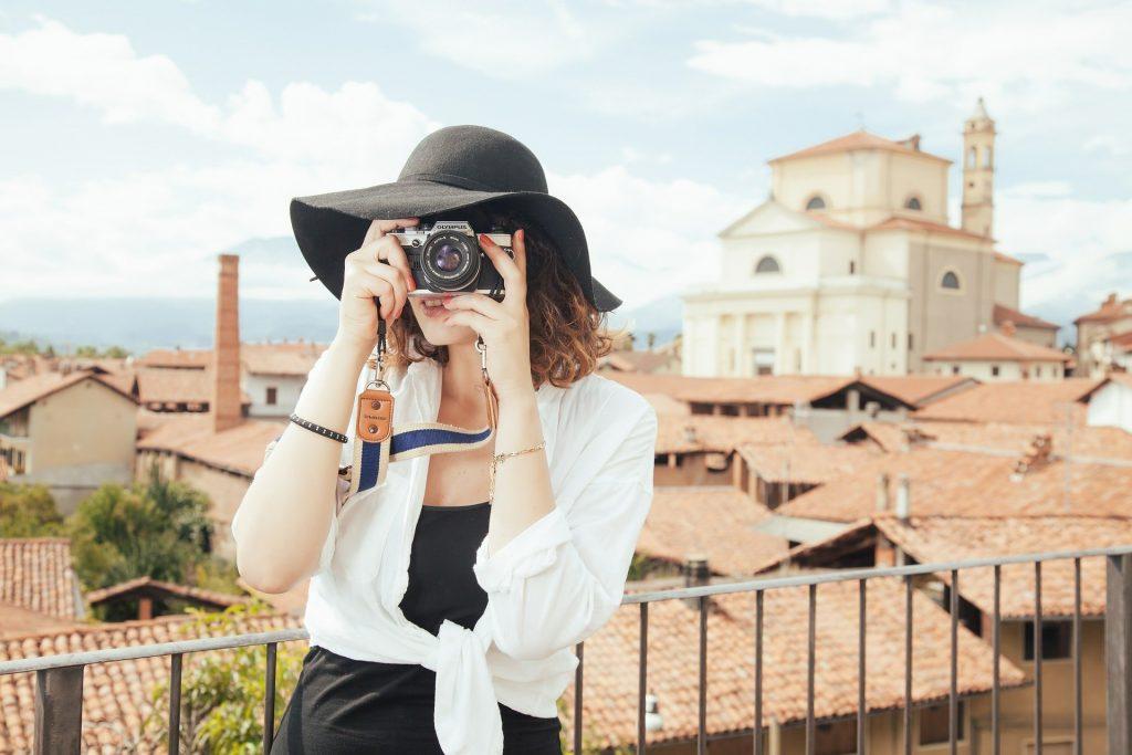 Imagem mostra uma mulher usando uma câmera fotográfica digital.
