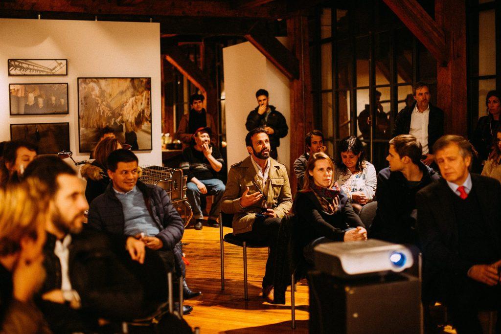 Auditório com pessoas sentadas e um projetor.