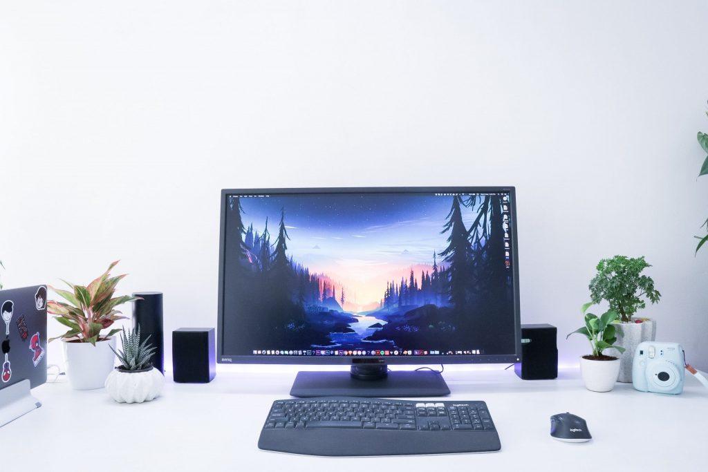 Imagem foca em um monitor com uma base larga apoiado sobre uma escrivaninha branca e repleta de pequenos vasos de plantes, além de alto-falantes e teclado e mouse sem fio.