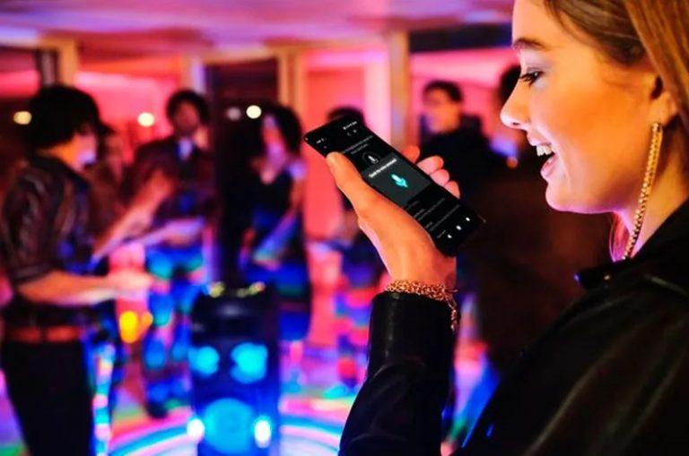 Mulher usando smartphone para controle mini system Sony em uma festa.