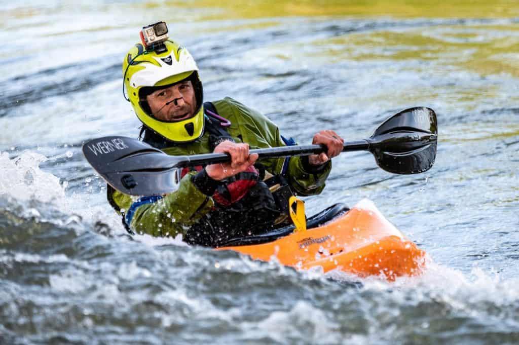 Na foto um homem em um caiaque dentro da água com uma GoPro no seu capacete.