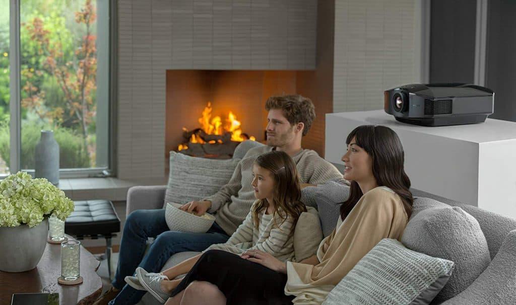 Imagem de uma família assistindo um filme em casa.