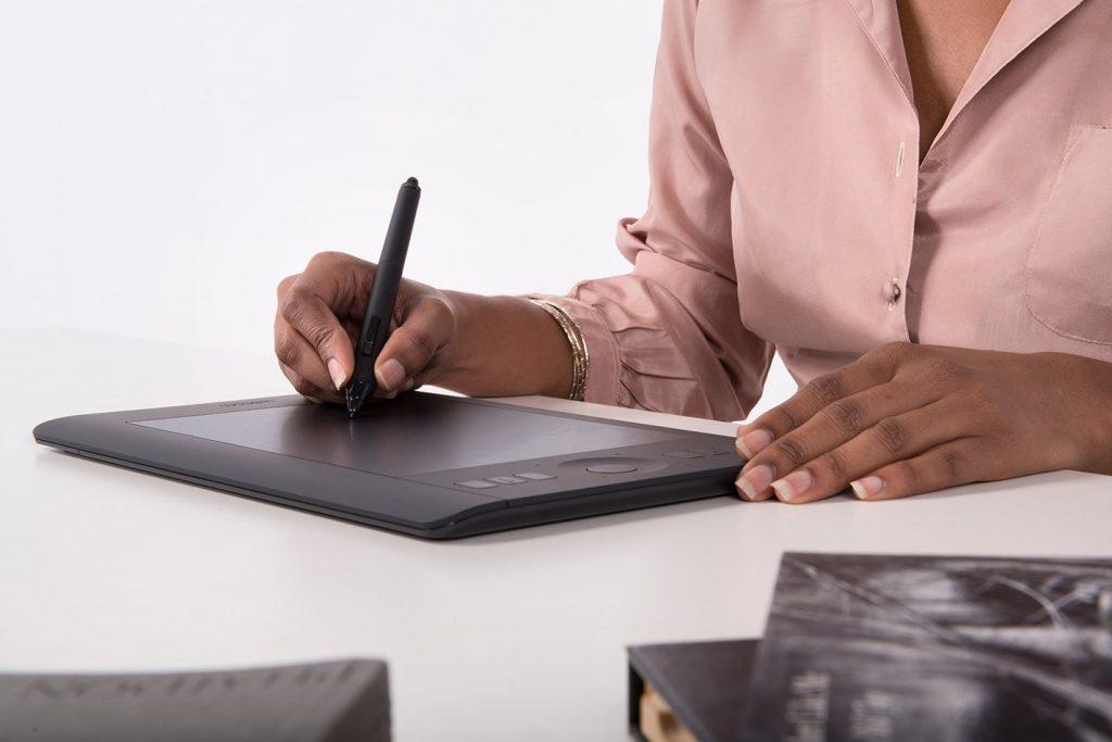 Imagem de uma mulher utilizando uma mesa digitalizadora.