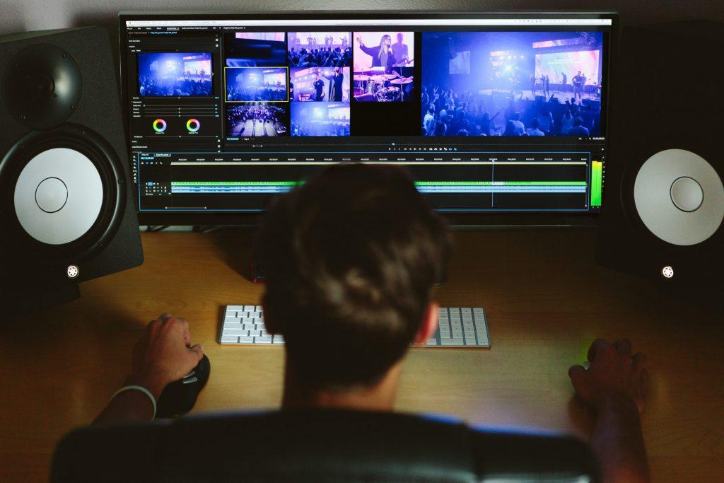 Imagem mostra, do alto, um rapaz editando um vídeo a partir de um monitor muito largo. Na mesma escrivaninha, grandes alto-falantes, um pequeno teclado sem fio e um mouse sem fio.