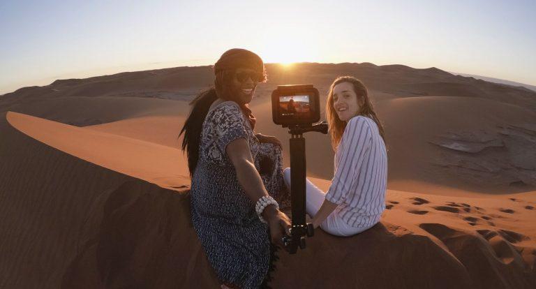 Duas pessoas fazendo selfie para registrar pôr do sol no deserto.