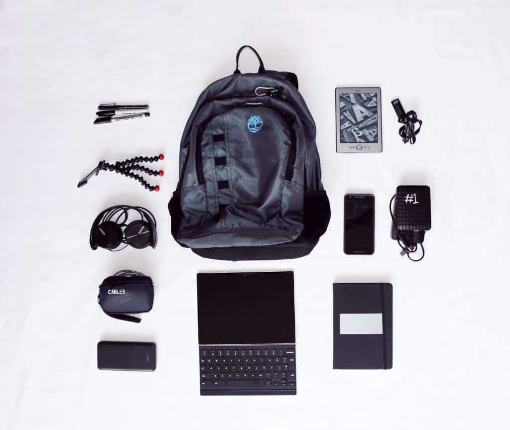 Imagem mostra uma montagem de itens eletrônicos em volta de uma mochila, incluindo um hd externo, à direita.