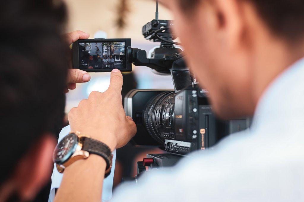 Na foto um homem de costas filmando com uma câmera Sony.