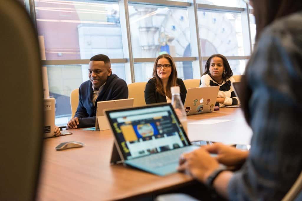 Imagem mostra três pessoas sentadas numa longa de mesa de reuniões, atrás de telas de notebooks e tablets. Em primeiro plano, mas desfocada, uma pessoa digita num pequeno teclado ligado à um tablet.