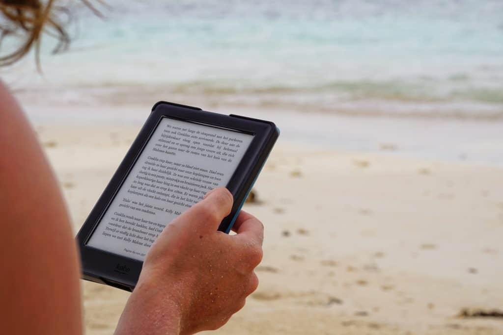 Imagem de uma mulher lendo um e-book em um Kindle na praia.