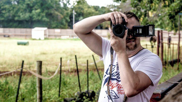 Homem ao ar livre, fotografando com câmera e flash Nikon.