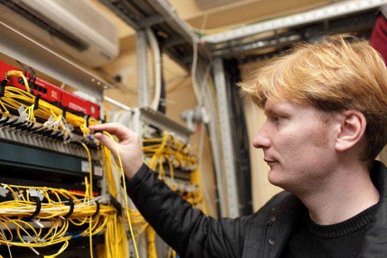 Imagem mostra um técnico instalando cabos de fibra ótica.