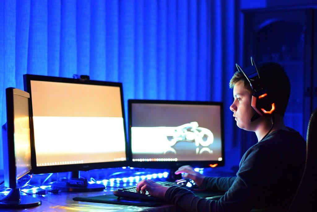 Imagem de jovem jogando no PC com um headset e três monitores
