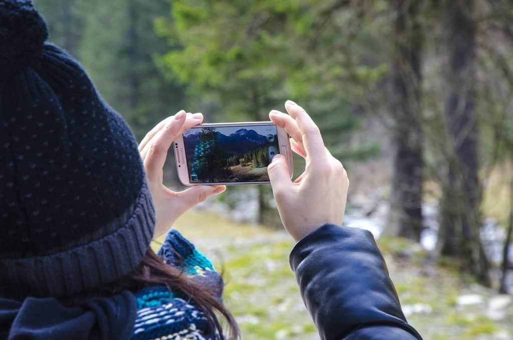 Imagem de uma mulher tirando uma foto com um smartphone da Samsung.