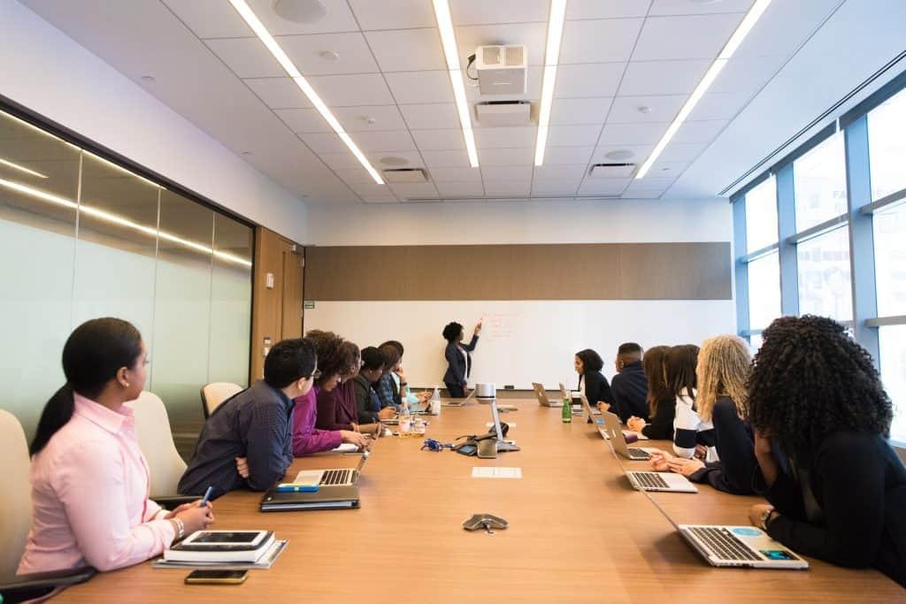 Na foto uma sala de reuniões cheia de pessoas com uma pessoa escrevendo em um quadro branco.