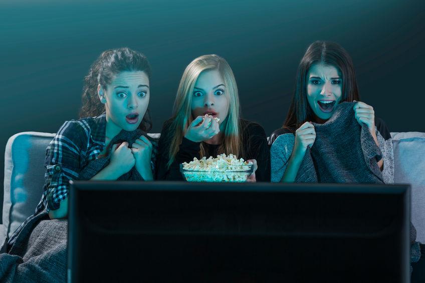 Três garotas comendo pipoca e assistindo filme do sofá.