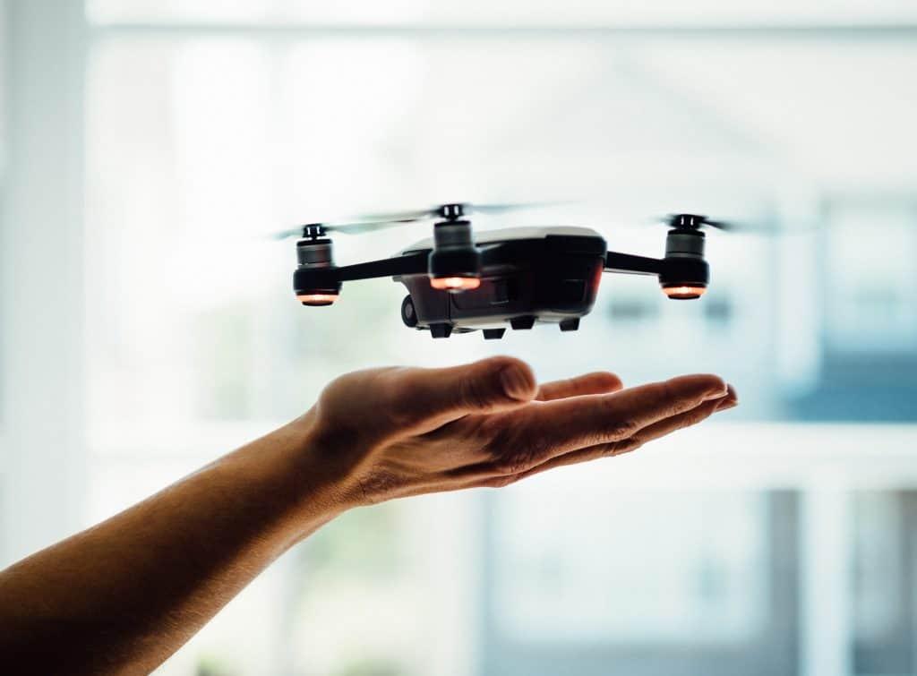 Imagem de um mini drone do tamanho da palma da mão de um homem.