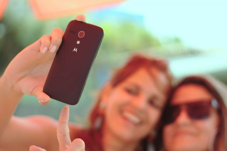 Duas mulheres tirando selfie com celular Motorola.