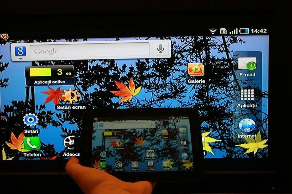 Na foto há a mão de uma pessoa segurando um tablet com uma televisão ao fundo transmitindo a tela do aparelho.