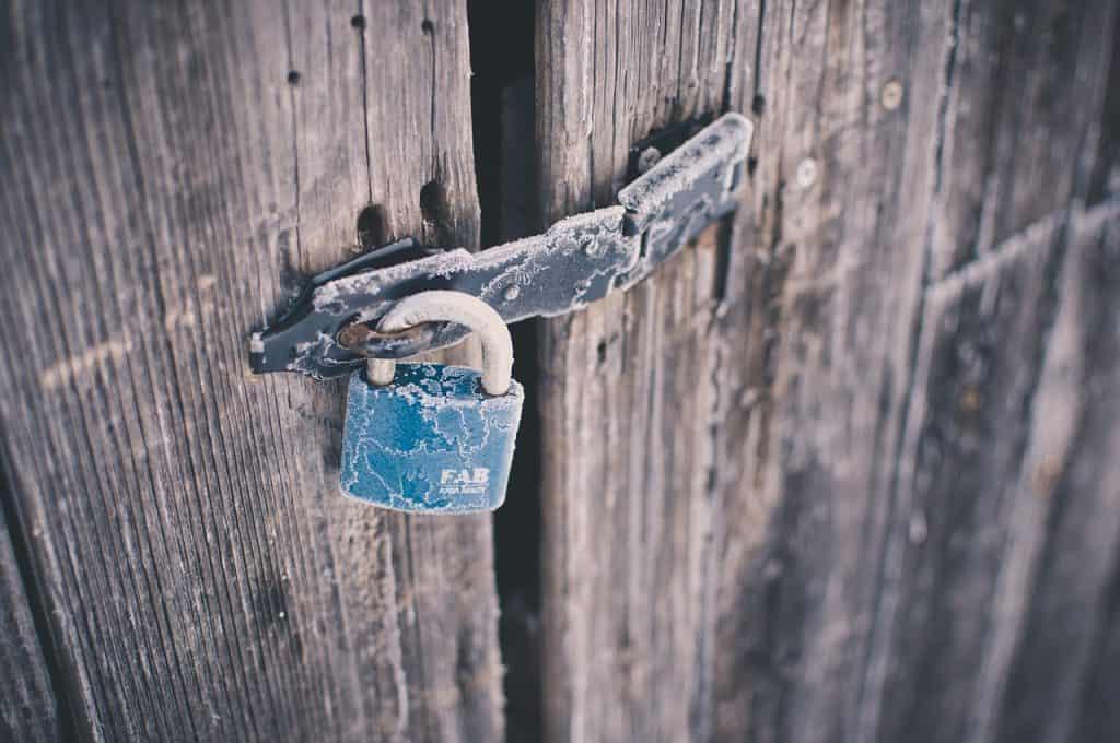 Imagem mostra uma porta de madeira trancada com um cadeado.