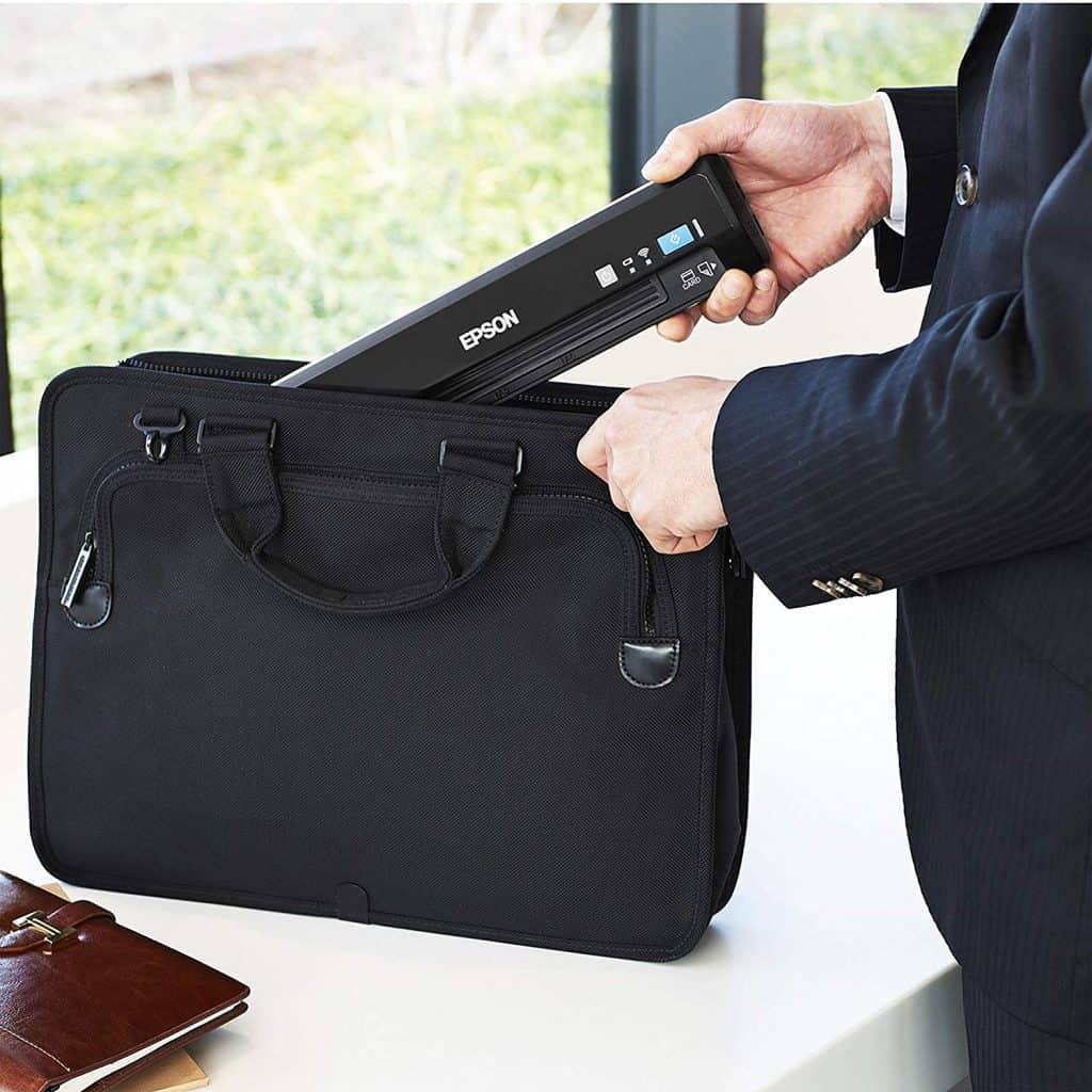 Imagem mostra um homem colocando um scanner portátil dentro de sua pasta de trabalho.