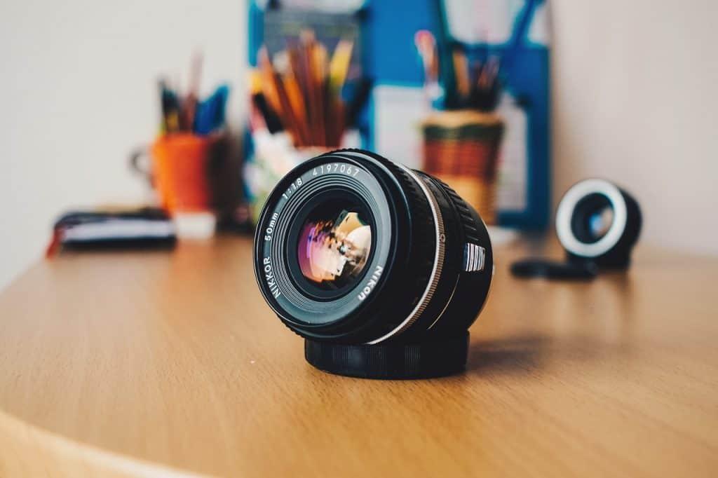 Na foto está uma lente Nikon em cima de uma mesa de madeira com alguns porta canetas ao fundo.