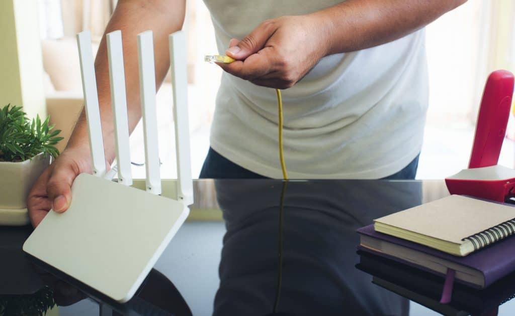 Homem conectando cabo de Wi-Fi no roteador.