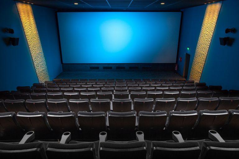 Imagem de sala de cinema com uma grade tela de projeção