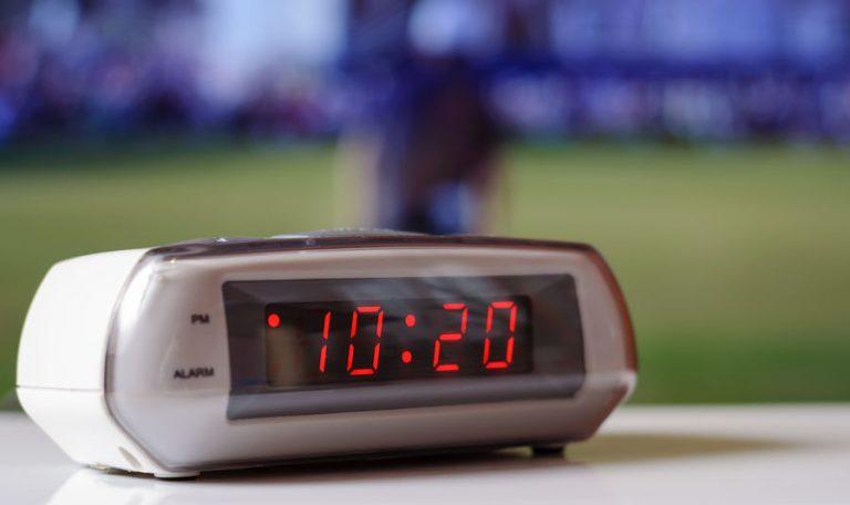 A imagem mostra um rádio-relógio com visor preto, marcando 10h20
