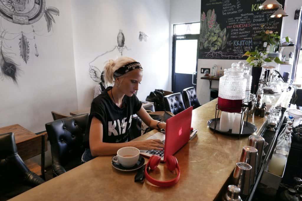 Imagem de uma mulher usando um notebook, ao lado um fone de ouvido da JBL.