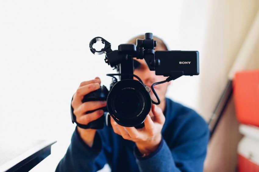 Homem gravando com filmadora.