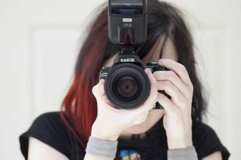 Mulher fotografando com câmera e flash da Nikon.