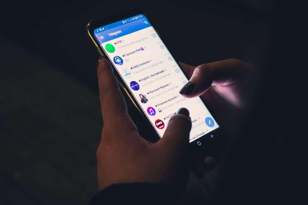 Imagem de uma mulher usando um smartphone a noite.
