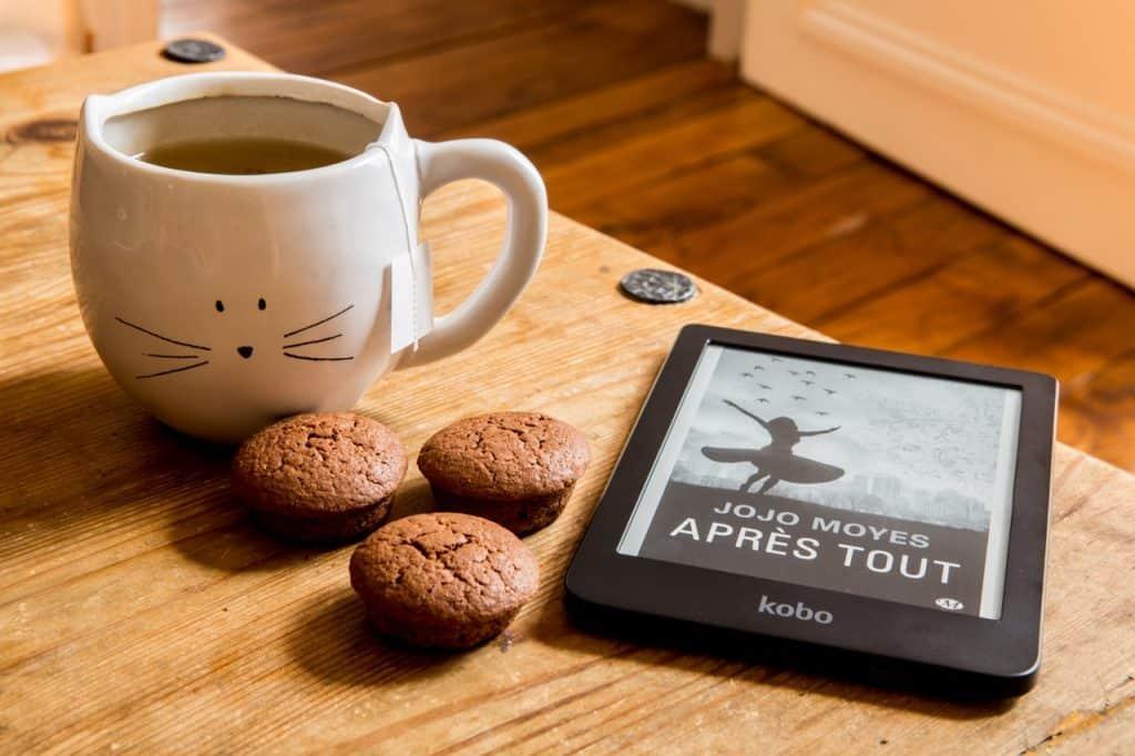 Na foto um e-reader ao lado de uma xícara e alguns bolinhos em cima de uma mesa de madeira.