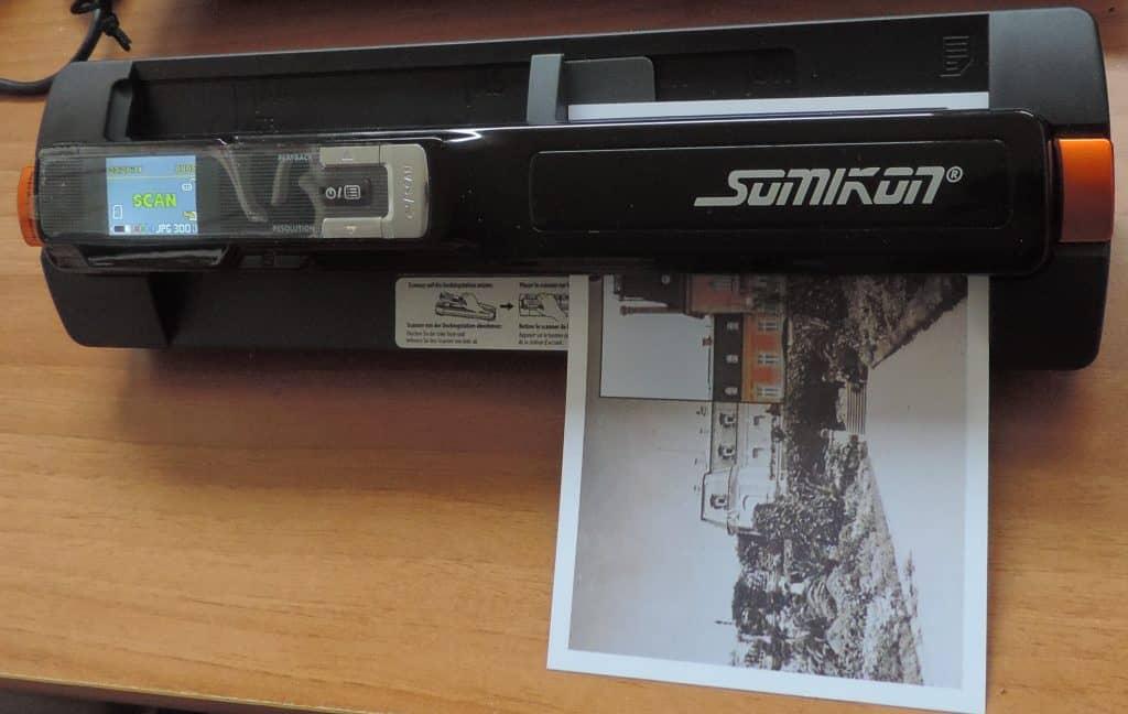 Imagem mostra um scanner portátil em cima de uma mesa fazendo a digitalização de uma foto.