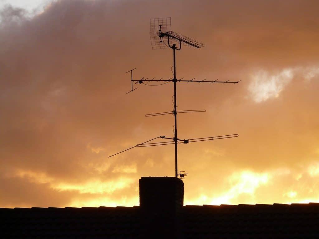 Na foto uma antena externa em cima de um telhado com o pôr do sol ao fundo.