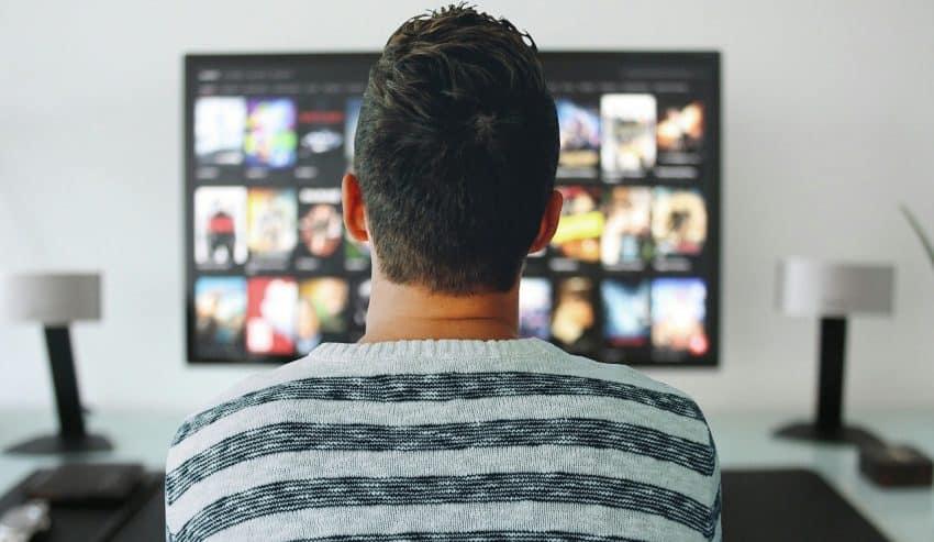 Imagem mostra homem de costas em uma sala em frente de uma televisão.