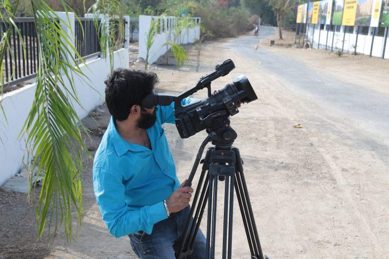 Homem filmando com filmadora no tripé.