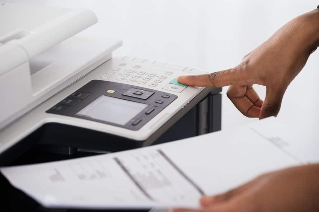 Mão masculina segurando papel e mexendo em impressora multifuncional.