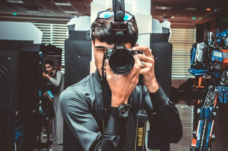 Homem fotografando com câmera e flash Nikon.